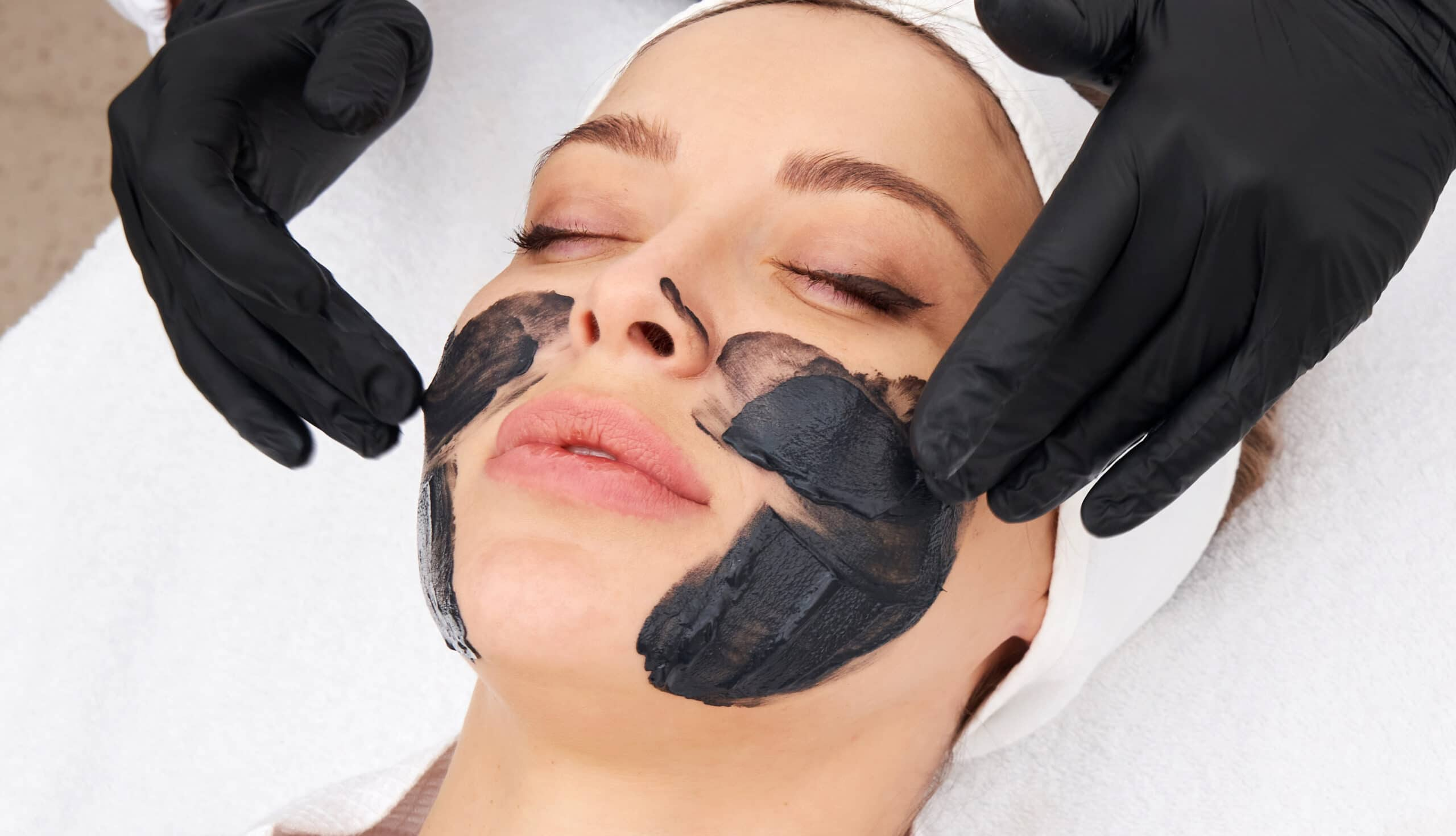 Cropped close up of a cosmetologist applying black mask on the face of a beautiful mature woman