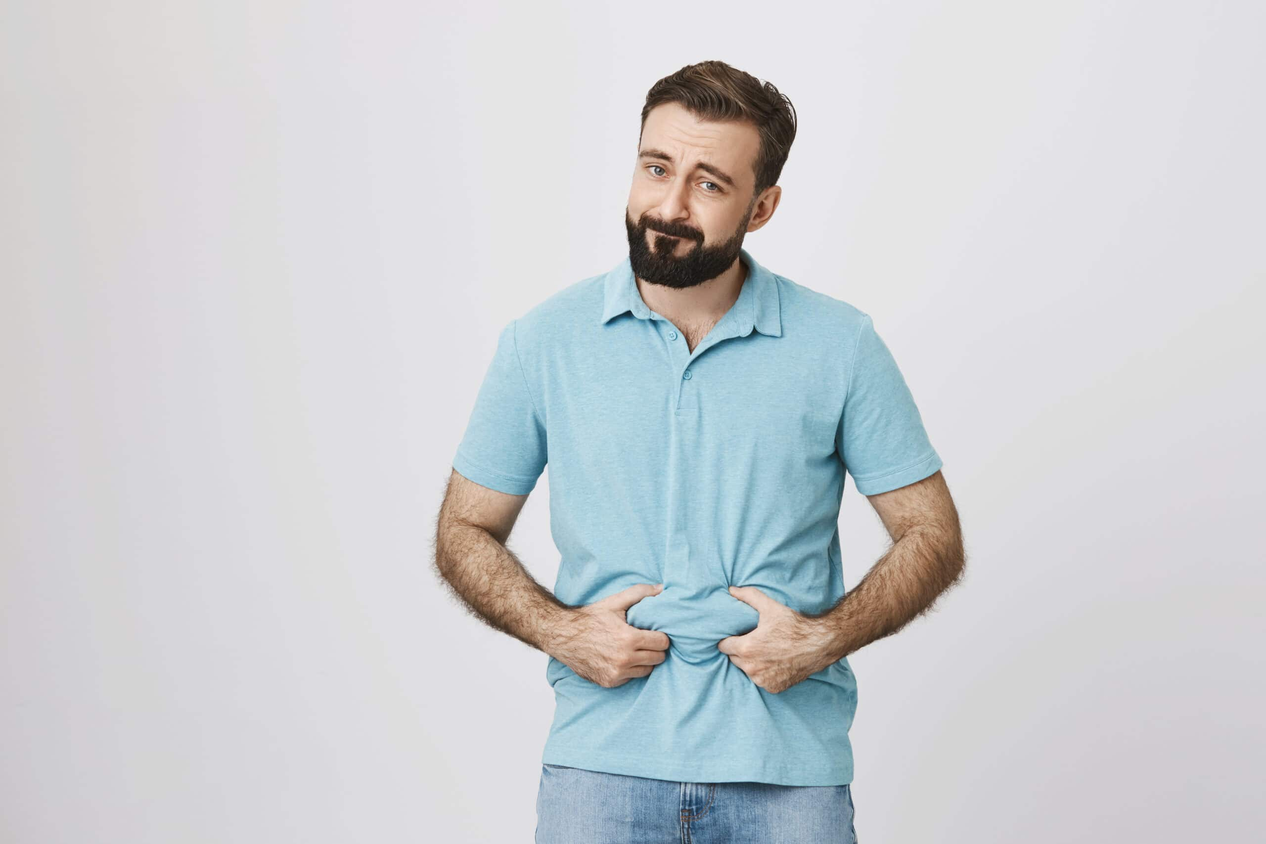 Picture of a bearded handsome man showing his beer belly over white background. Person is bothered because of his extra weight so he decides to sit on diet.