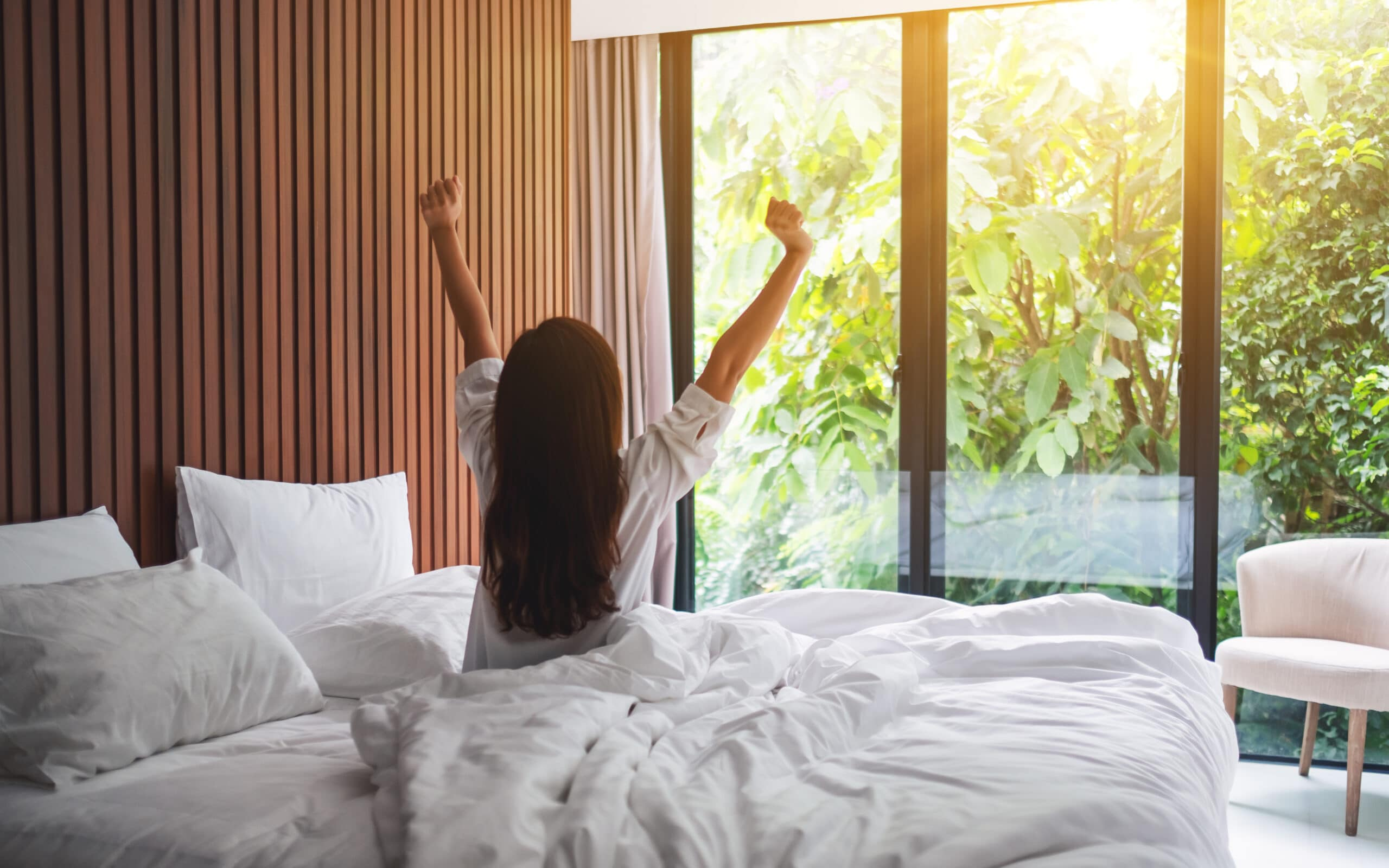 Rear view image of a woman do stretching after waking up in the morning , looking at a beautiful nature view outside bedroom window