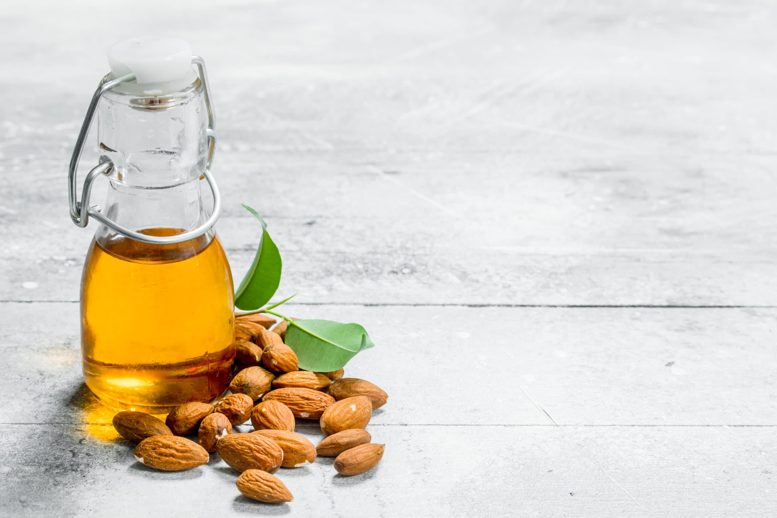 Almond oil in a glass bottle . On a rustic background.