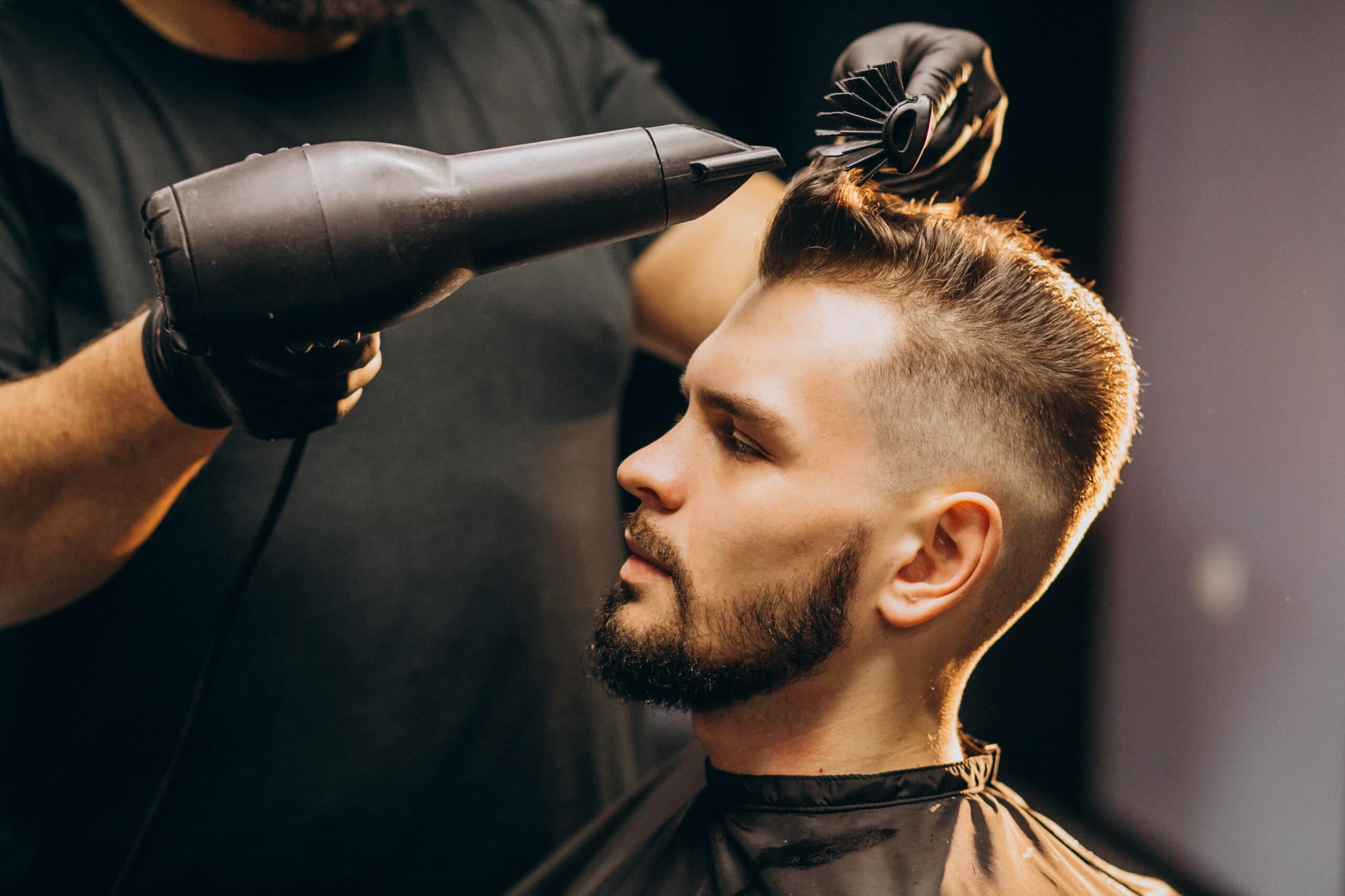 Handsome man at a barber shop styling hair