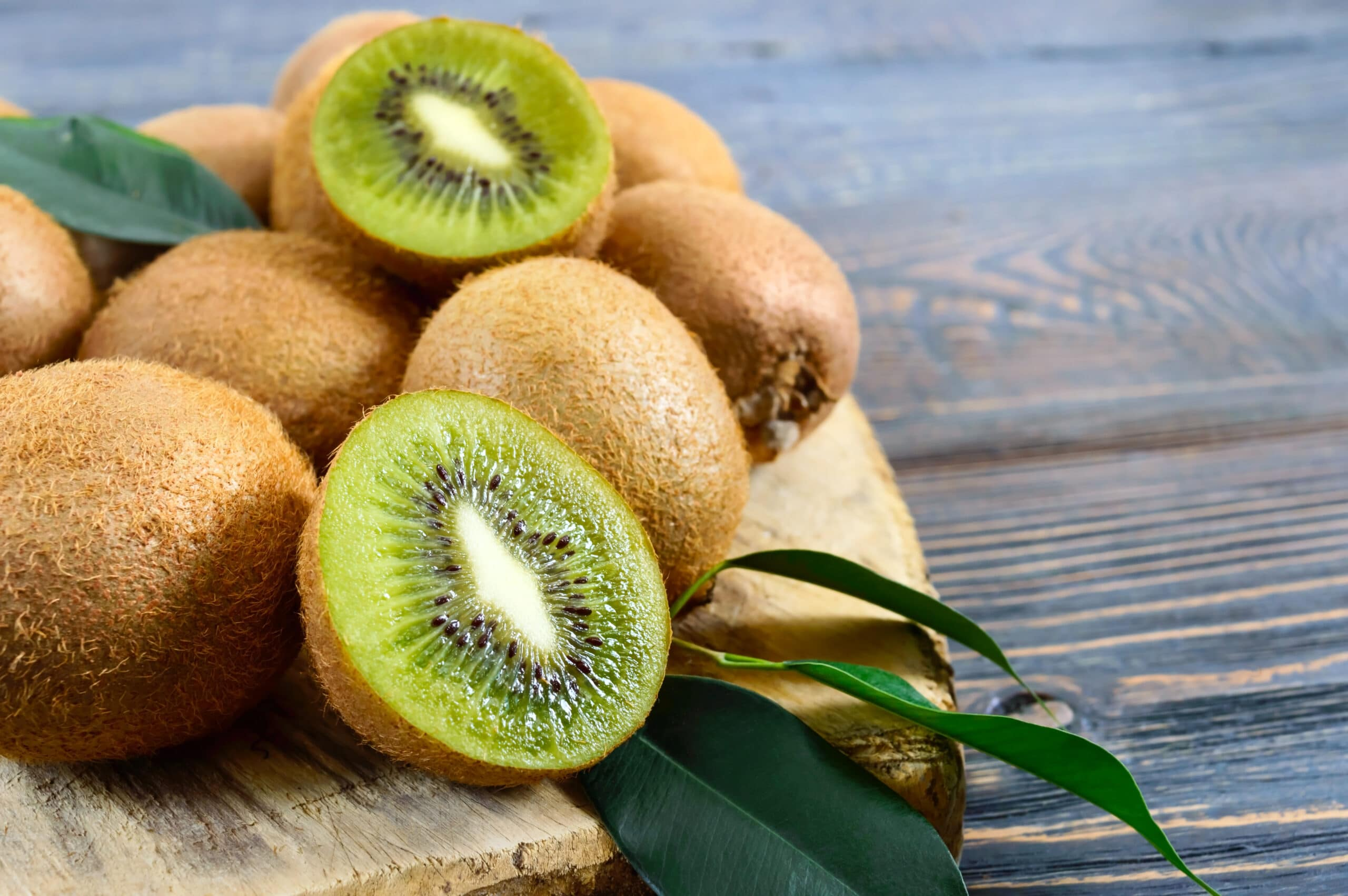 Ripe fruits of kiwi whole and halves are scattered on a cutting board with an old knife on a wooden table.