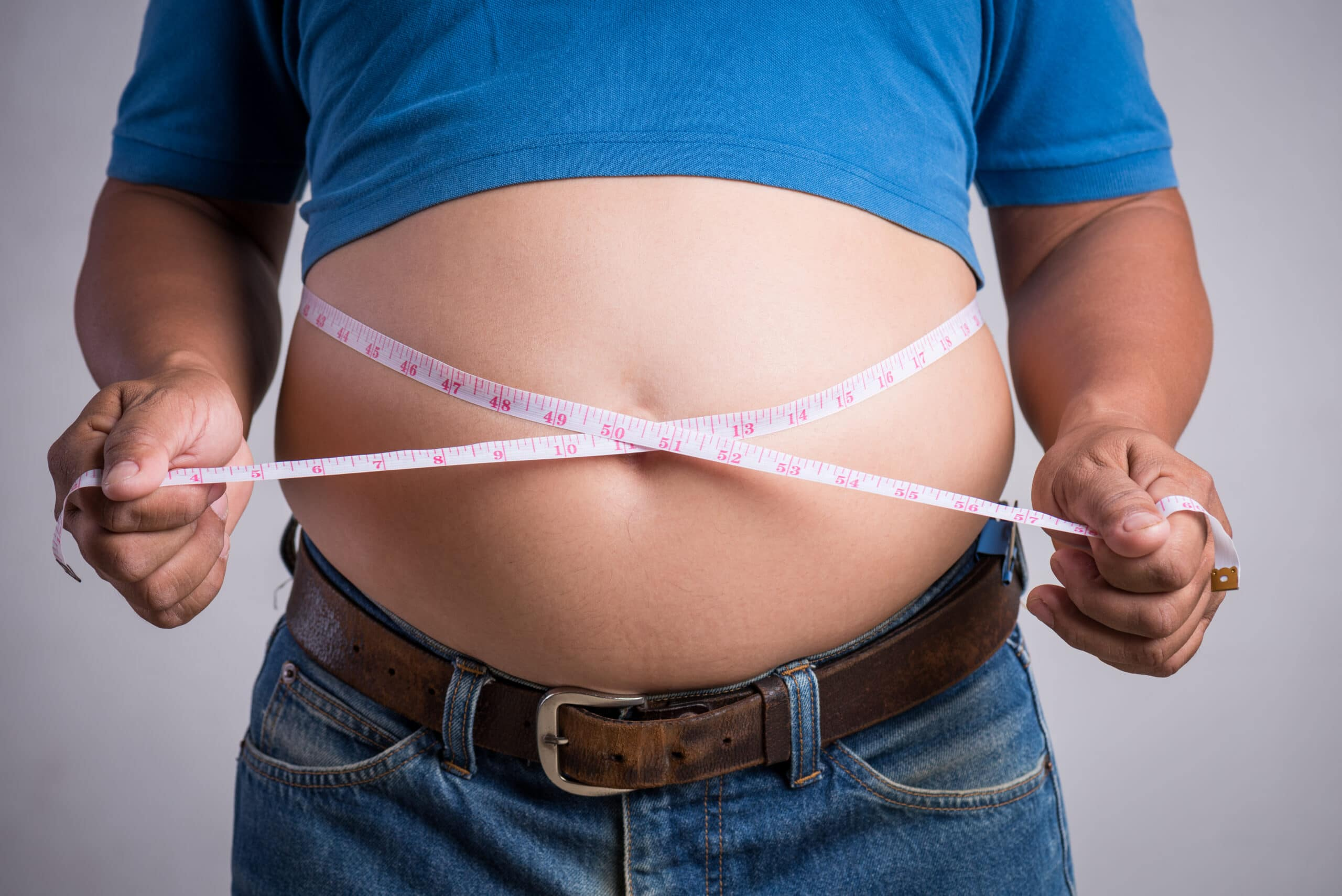Overweight or fat adult man in very tight jeans with measuring tape on a gray background. Healthcare, medicine concept.