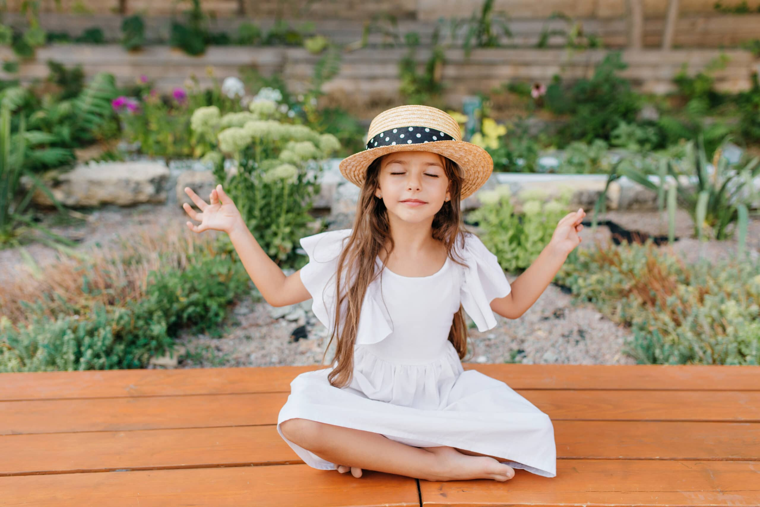Pretty brunette female kid in straw hat sitting near flowerbed in lotus pose with eyes closed. Little girl in white dress doing yoga in garden on beautiful nature background.