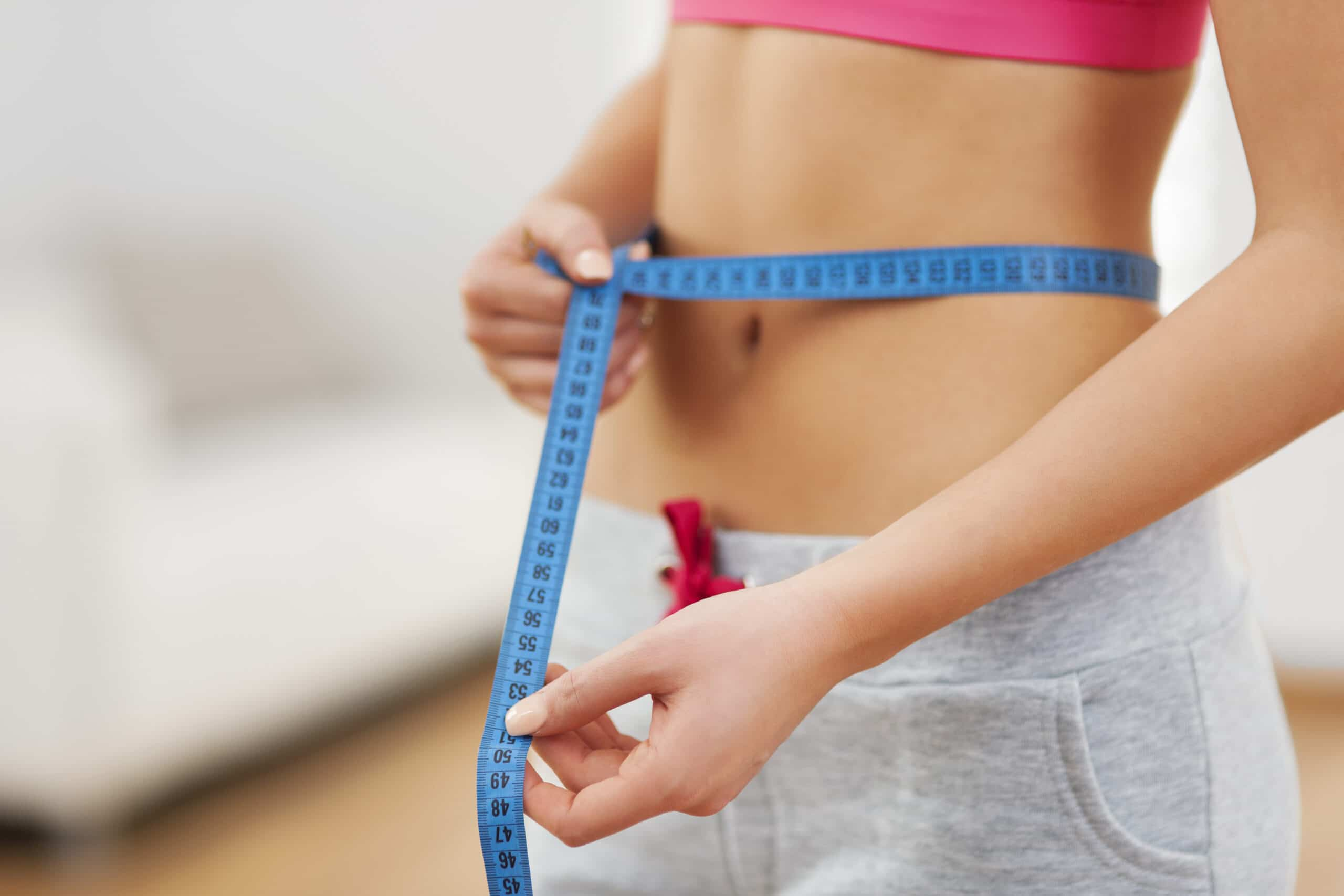 Slim woman with measuring tape