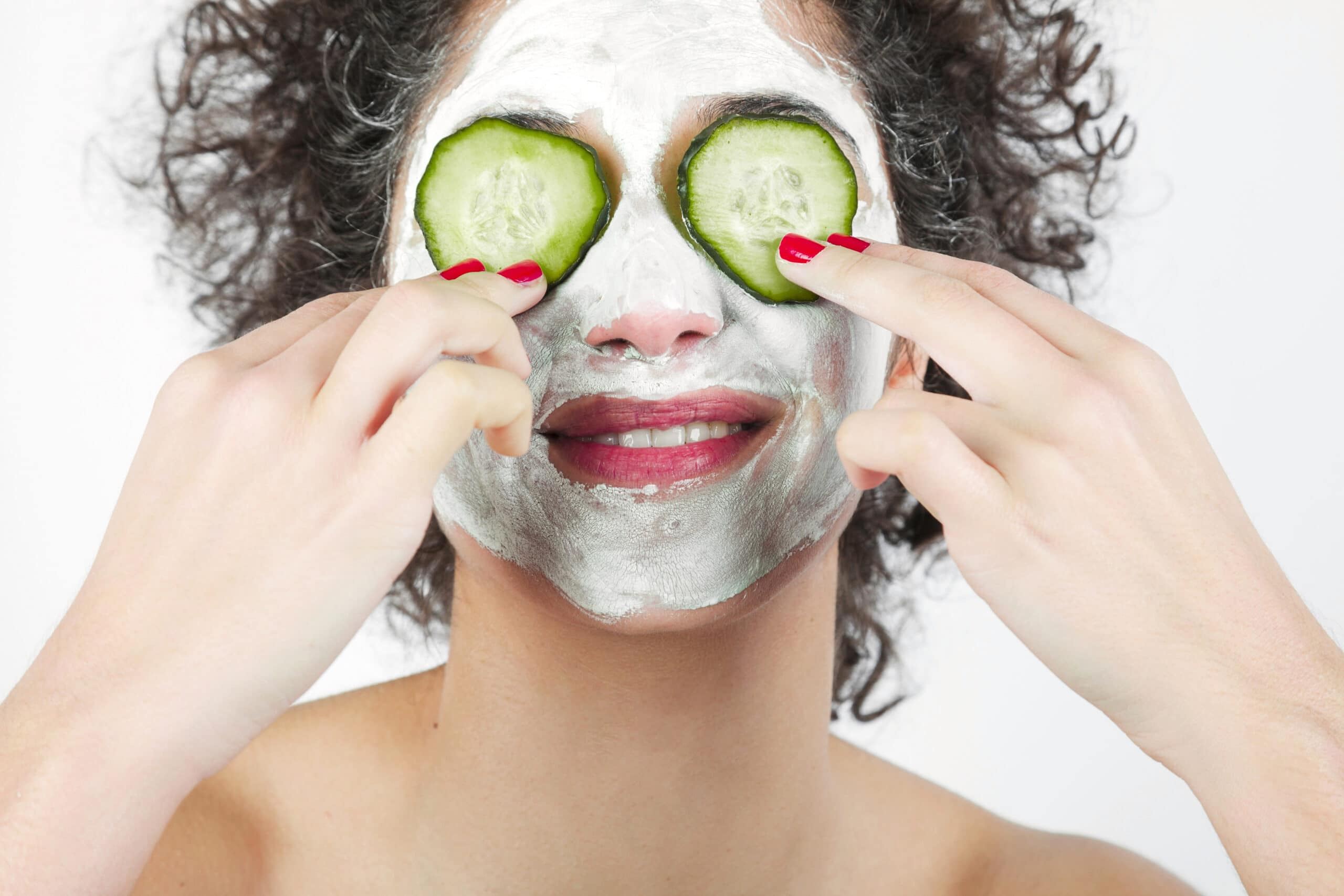 smiling-young-woman-with-face-mask-putting-cucumber-slices-her-eyes