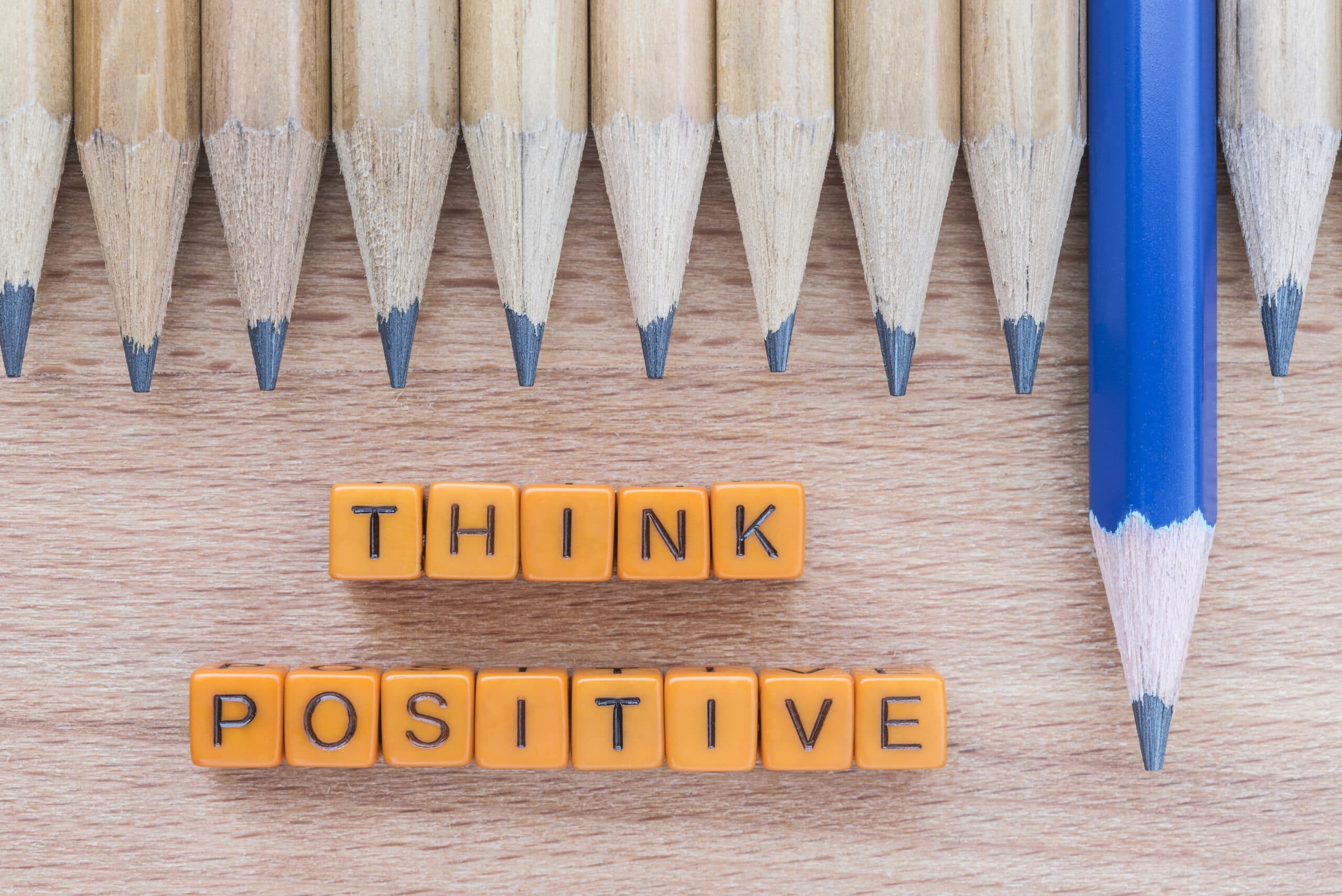 Words Think Positive motivational slogan on wooden table with group of pencils. Top view